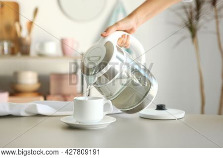 Pure Water Boils In An Electric Kettle On The Table In The Kitchen