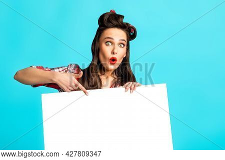 Shocked Pinup Lady Pointing At Blank Banner On Blue Studio Background, Mockup For Ad, Promo, Sale