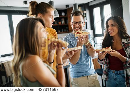 Group Of Friends Having Party At Home, Eating Pizza And Having Fun.