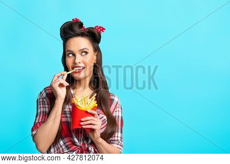 Young Pinup Woman In Retro Outfit Eating French Fries From Package, Looking Aside At Empty Space On