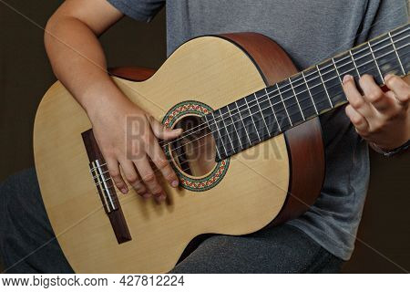 Hands Of Boy Playing An Acoustic Guitar, Close-up. Acoustic Guitars Are Playing. Musical Concept. Ac