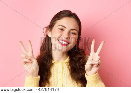 Close Up Of Beautiful Young Woman Showing Peace V-sign And Smiling Happy At Camera, Wearing Bright G