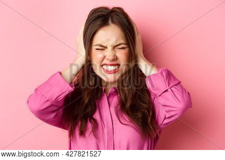 Close Up Of Pissed-off And Angry Woman Grimacing Bothered, Shut Her Ears With Hands From Loud Bother