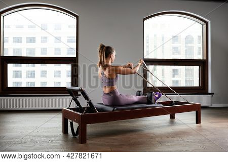 Young Girl Doing Pilates Exercises With A Reformer Bed. Beautiful Slim Fitness Trainer On A Reformer