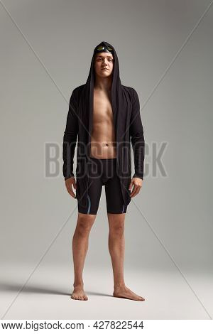 Guy Swimmer In A Cap, Mask And Bathrobe For Swimming, On A Gray Background, Preparing For The Swim