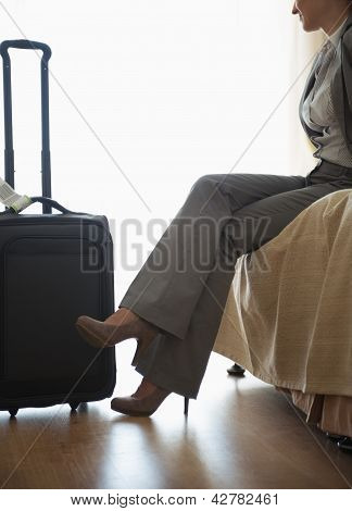 Tired Business Woman Sitting On Bed In Hotel Room After Trip