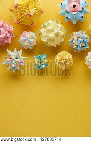 Set Of Multicolor Handmade Modular Origami Balls Or Kusudama Isolated On Yellow Background. Visual A