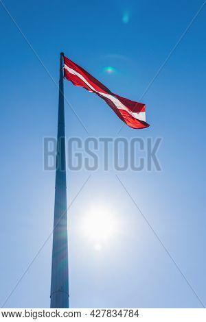 Latvian National Flag On A Blue Sky Background. Photographed Against The Sun.