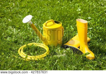 Gardening Yellow Tools Outdoor In Garden. Rubber Boots, Watering Can, Hose.