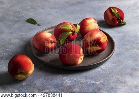 Several Ripe Peaches Or Nectarines Lie On A Black Ceramic Plate On A Blue Plaster-textured Surface.