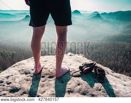 Barefoot Slender Legs With Hairy Calves Of A Male Runner Standing Next To Removed Sweaty Running Sho