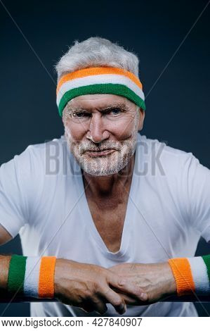 Portrait Of A Handsome Gray Haired Senior Man With Sports Headband. Sport And Health Care Concept