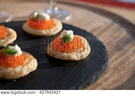 Tasty Appetizer For Dinner, Small Pancakes Bliny With Red Fish Caviar  Served Outdoor