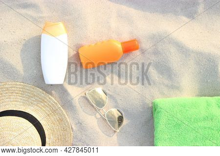Beach Accessories And Sunscreens On The Sand Of The Seaside