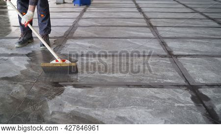 The Tiler Washes The Tiles After Work. The Master Washes The Tiles After Grouting.