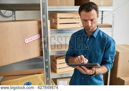 Waist Up Portrait Of Young Man Using Digital Tablet In Warehouse While Doing Inventory And Managing