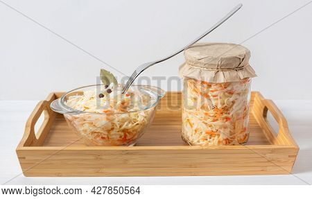 Sauerkraut In A Jar And A Bowl. Sauerkraut With Carrots In A Wooden Tray On A White Background. Ferm