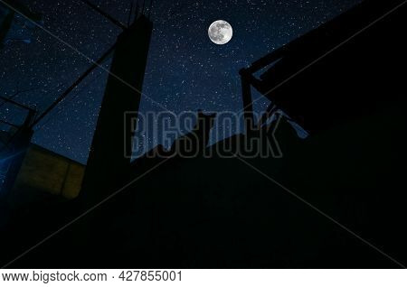 Cat Sit On Wall In Moonlight And Looking At Full Moon. The Roof Of Building Cat Silhouette At Night.