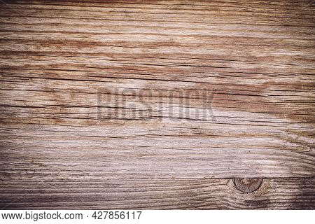 Close-up Of A Wooden Plank With Cracks And Damage. Aged Material. Lack Of Wood Protection. Wood Text
