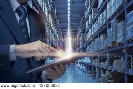 Businessman Use Tablet To Plan, Check, Control Of Logistics Transportation In Warehouse. Business Ma