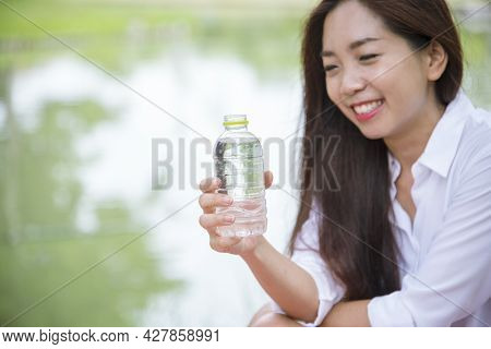 Happiness Beautiful Asian Chinese Women Holding Mineral Water Bottle. Young Woman Drinking Water Fro