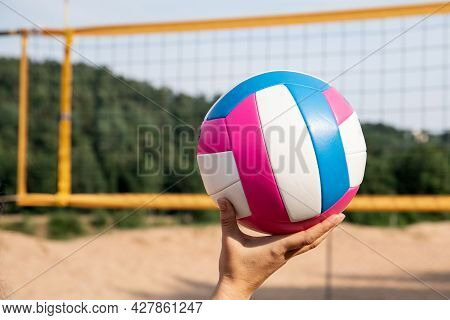 Colorful Beach Volleyball Ball In A Womans Hand. Volleyball Court And Net On The Beach