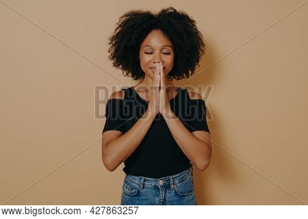 Afro American Young Woman Praying And Holding Hands In Prayer Gesture Standing Isolated On Dark Beig
