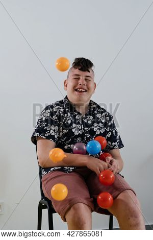 Happy Teenage Child Over White Wall In Rehabilitation Center. Boy With Cerebral Palsy Smiling, Playi