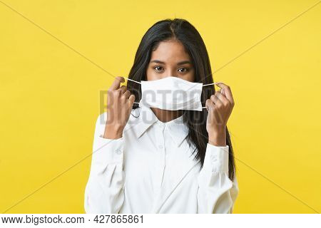 Asian Woman Holding Facemask And Smiling After Getting Vaccine Behind The Mask Which Is Using For Pr