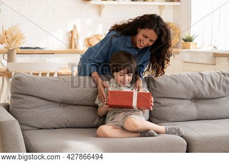 Excited Little Boy Receiving Birthday Present From Mum Sitting On Sofa In Living Room. Children Holi