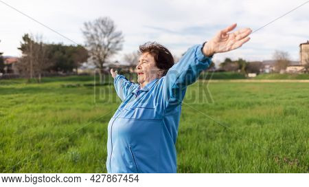 Concept Of A Healthy Lifestyle And Sports. Happy Elderly Woman In Sports Clothes, Doing Sports In Th