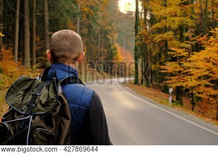 Autumn Hikes. Autumn Travel And Walks.traveler With A Backpack Walks Along The Road In The Autumn Fo