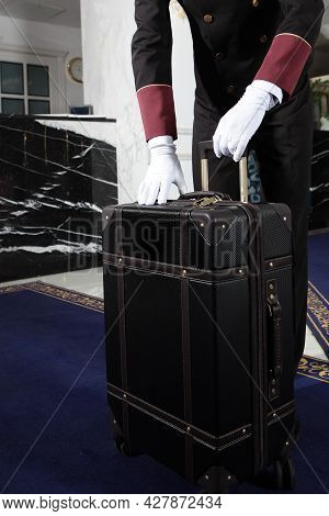 A Uniformed Doorman Holds A Brown Leather Suitcase In His Hand. Doorman's Hands In White Cotton Glov