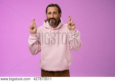 Nervous Unsure Hopeful Handsome Bearded 40s Man In Pink Stylish Hoodie Cringing Worried Cross Figers
