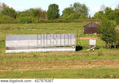 Elongated Homemade Plastic Greenhouse Covered With Partially Open Semi-transparent Nylon Next To Whi