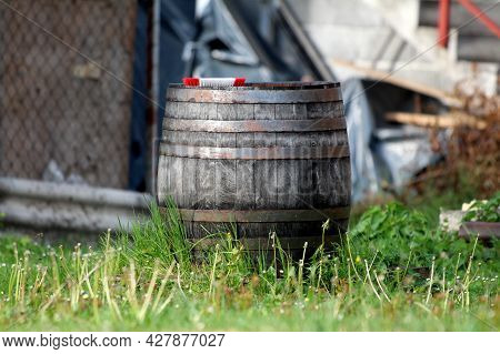 Retro Vintage Old Large Wooden Wine Barrel With Rusted Metal Hoops And Dilapidated Wooden Boards Lef