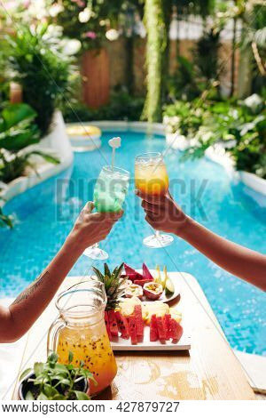 Female Friends Relaxing In Chaise-lounges By Swimming Pool And Clinking Glasses Of Delicious Fruit C