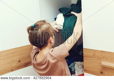 Young Boy Throwing Dirty Clothes In Closet. Mess In Wardrobe And Dressing Room. Untidy Disoreder Clo