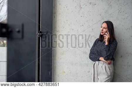Portrait Of Mid Adult Businesswoman Standing Indoors In Office, Using Smartphone.