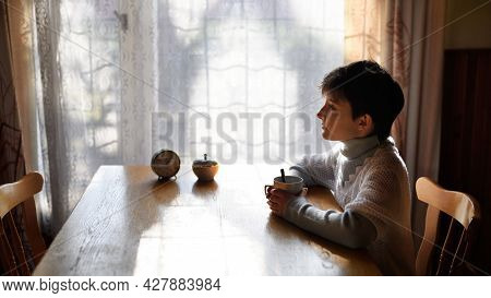 Poor Sad Small Girl With Tea Sitting At The Table Indoors At Home, Poverty Concept.