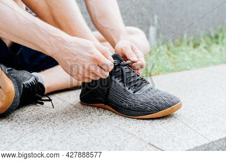 Close Up Sports Man Tying Shoelace While Running Outdoors.