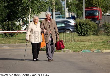 Moscow, Russia - July 2021: Elderly Man And Woman With Cane Walking Down The City Street. Old Couple