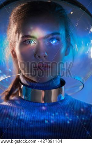Beautiful tender girl with blue eyes in a glass spacesuit looks at camera against the background of outer space. Space concept. Copy space.