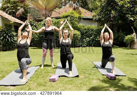 Fitness Trainer Controlling Young Women Making Crescent Lunge On Yoga Mats In Backyard Of Getaway Sp