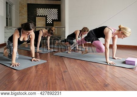 Group Of Fit Young Women Doing Knee To Forehead Exercise To Strengthen Core Muscles During Yoga Clas
