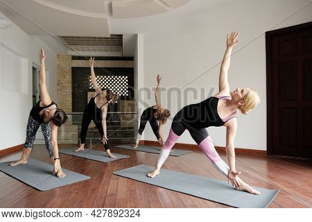 Fit Flexible Women In Workout Clothes Attending Yoga Class And Doing Triangle Pose That Stimulates F