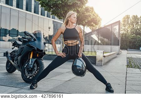 Mid Adult Woman Athlete Posing Around Building And Motorbike