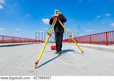 Surveyor Engineer Is Measuring Bridge Under Construction, Site. Surveyors Ensure Precise Measurement