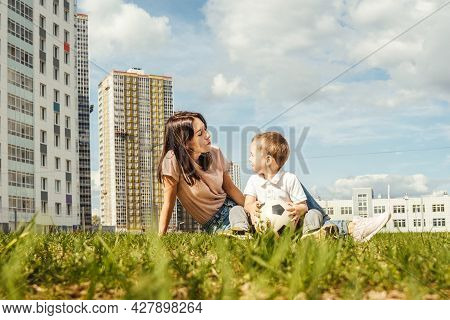 Portrait Of Mother With Son On Grass.