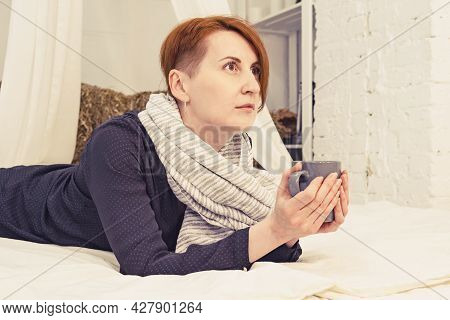 Young Red-haired Woman Lies On The Bed With A Cup Of Tea In Her Hands And Looks Thoughtfully Into Th